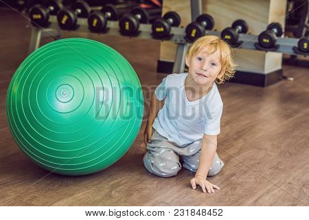 The Boy Is Sitting Near The Fitball In The Gym.
