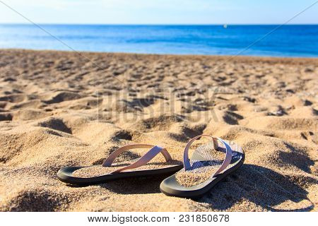 Beach Shoes On Hot Sand. Female Summer Sandals In Holiday Vacation. Blue Sea Coastline Travel.