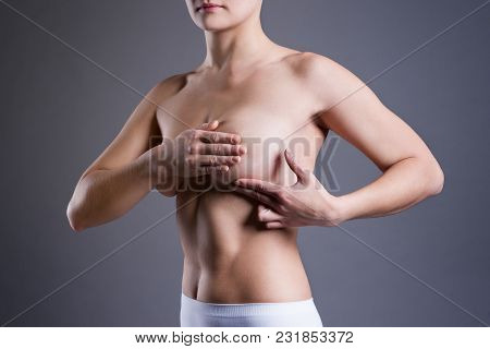Woman Examining Her Breasts For Cancer, Pain On Female Body, Studio Shot On Gray Background