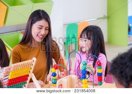 Asian Female Teacher Teaching Mixed Race Kids Play Toy In Classroom,kindergarten Pre School Concept.