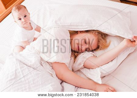 Cute Baby Girl Came To Wake Sleepy Mom, Which Sleeping On A White Bed