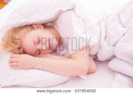 Beautiful Woman Sleeping In White Bed, Her Hands Beside Her Head