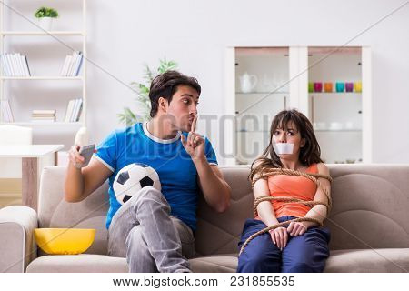 Man tying up his wife to watch sports football