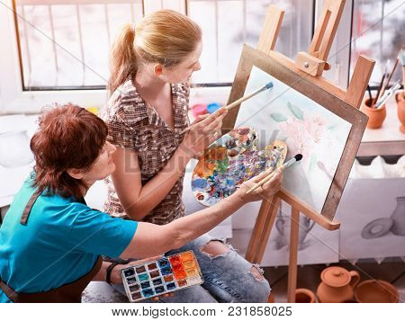 Artist painting easel in studio. Authentic grandmother and kids girl paints palette morning sunlight. Compatible creativity solving psychological problems. Training of pupils by elderly professional.