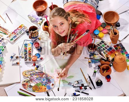 Authentic artist children girl paints with set palette watercolor paints palette and brush in morning sunlight. Painting in studio on floor. Best choice of brushes for watercolor painting.