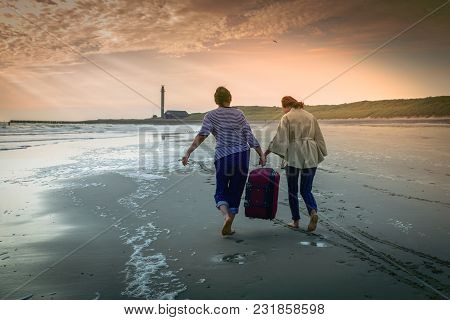 Two Middle-aged Women With Bare Feet And Heavy Luggage Walk Along The Wet Sand Along The Coast To Th