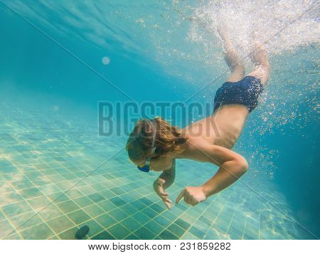 A Child Boy Is Swimming Underwater In A Pool, Smiling And Holding Breath, With Swimming Glasses.