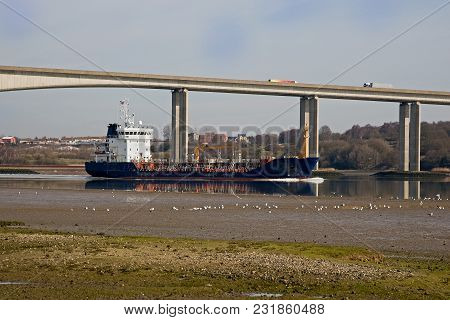 A Ship Carrying Gas Passing Under A Motorway Bridge At Low Tide In The Uk