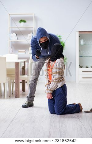 Armed man assaulting young woman at home