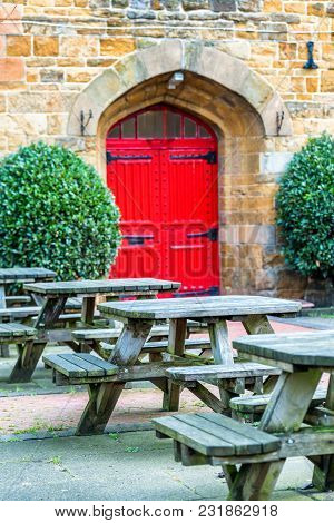 Day View Of Empty Typical Pub Garden With Tables And Red Antique Doors In England .