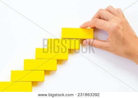 Concept Of Building Success Foundation. Women Hand Put Red Wooden Block On Yellow Wooden Blocks In T