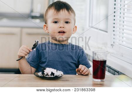 A Small Child Eats Black Chocolate Cake, At Home In The Kitchen Next To The Red Juice Of Pomegranate