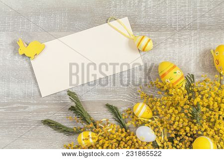 Easter Accessories, Mimosa And Yellow Daffodils On A Light Wooden Surface. Yellow Orange Easter Conc