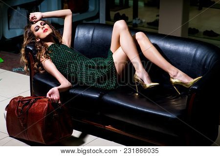 Sexy Woman Relax On Sofa With Purchase In Shop. Fashion Girl With Leather Bag Tired Shopping. Shoppi