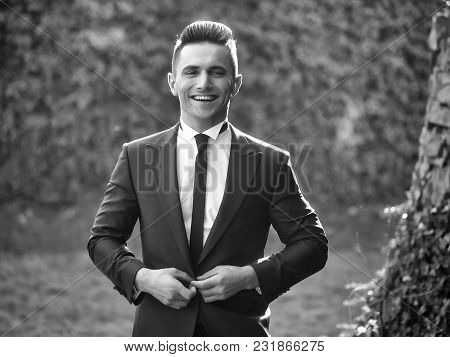 Man Young Handsome Elegant Model Buttons Suit Coat With Black Skinny Necktie Smiles Looks In Camera