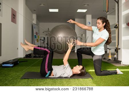 Physical Therapist Assisting Young Caucasian Woman With Exercise With Yoga Ball During Rehabilitatio