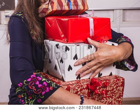 Woman Holding Many Gift Boxes. Hands Full. Giving A Gifts.