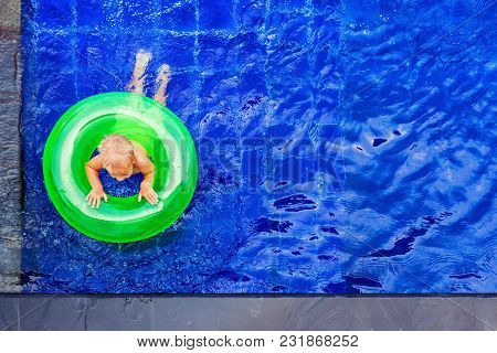 Funny Photo Of Baby Boy Swimming With Fun On Inflatable Swim Ring In Clear Aqua Park Pool. Top View.