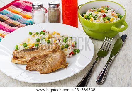 Fried Pork Schnitzel With Vegetable Mix In Plate, Knife, Fork, Ketchup In Bottle, Salt, Pepper On Wo