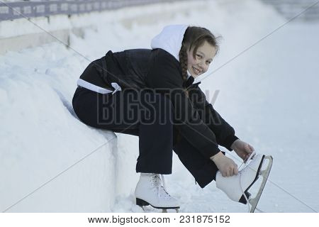 Teenage Girl Sitting On Snow Tightening The Laces On The Skates, Youth Pastime And Rest