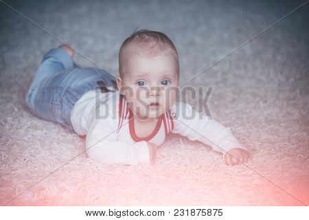 Innocence, Beauty, Purity. Infant Crawl On Floor Carpet. Childhood, Infancy, Newborn. Baby With Blue