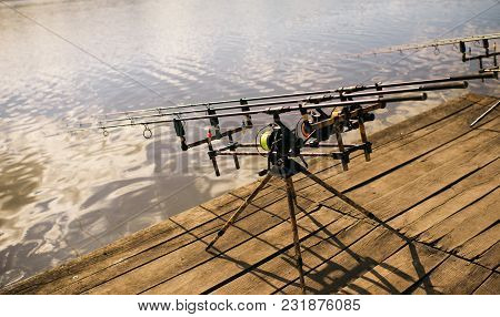 Reels And Rods At River Or Lake Water. Reels And Rods On Pod On Wooden Pier.