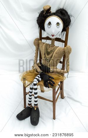 Creepy Steampunk Rag Doll Sitting On Wooden Chair. Looking Ahead. Lifesize Doll On A Grungy White Ba