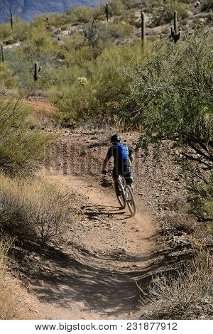 An Unidentified Biker Leaves A Trail Of Dust As He Drives Down A Rocky Path Through A Mountainous An
