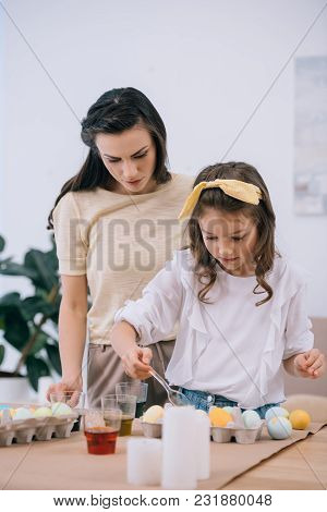 Mother And Little Daughter Painting Easter Eggs Together