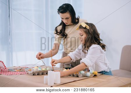 Mother And Adorable Daughter Painting Easter Eggs Together