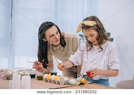 Young Mother And Daughter Painting Easter Eggs Together