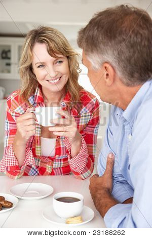 Mid age couple having coffee at home