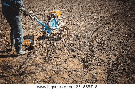 The Man Plows The Land With A Cultivator