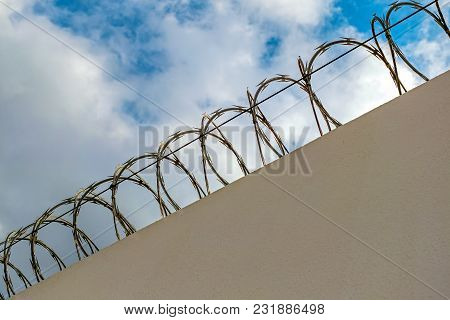 Concrete Fence With Barbed Wire Against Cloudy Sky