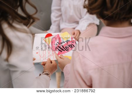 Cropped Shot Of Children Presenting Mothers Day Greeting Card For Mother