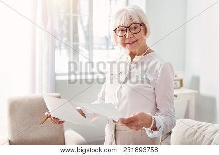 Best Professional. Upbeat Elderly Woman In Eyeglasses Studying Documents With Research Results While