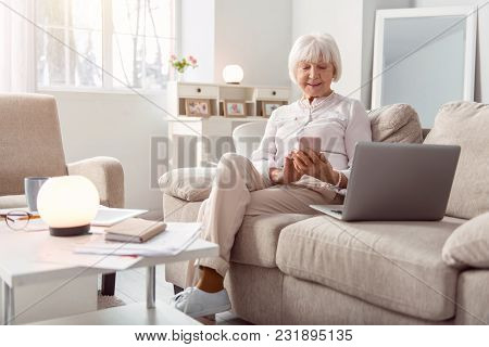 Pleasant Chat. Beautiful Elderly Woman Texting On Her Phone And Smiling Happily While Sitting On The