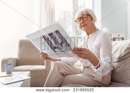 Interesting Article. Beautiful Senior Lady Sitting On The Sofa In The Living Room And Reading A News