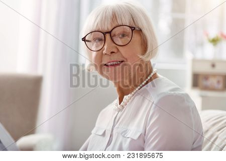 Great Mood. The Close Up Of A Pleasant Joyful Senior Lady In Eyeglasses Smiling At The Camera While
