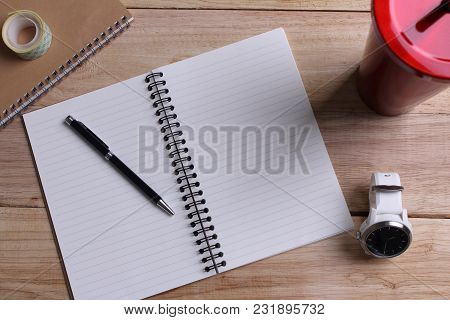 Top View Open Book With Blank Pages And Pen With Clock With Stainless Steel And Tumbler Cup On Woode