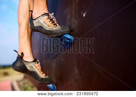 Bottom Close Up View Of Rock Climber Foot On Training Artificial Climbing Wall. Male Feet In Climbin