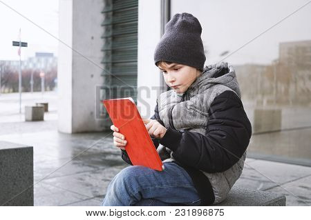 7 Year Old Boy Playing Online Game On Tablet Computer While Sitting Outside Alone On City Street In