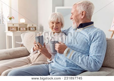 Precious Relationship. Happy Elderly Couple Sitting On The Couch And Bonding To Each Other While Dri