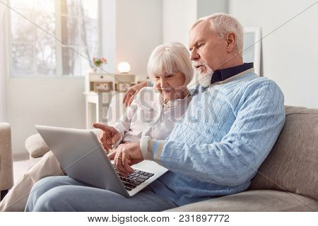 Doing Everything Together. Cheerful Elderly Couple Sitting On The Couch In The Living Room And Choos