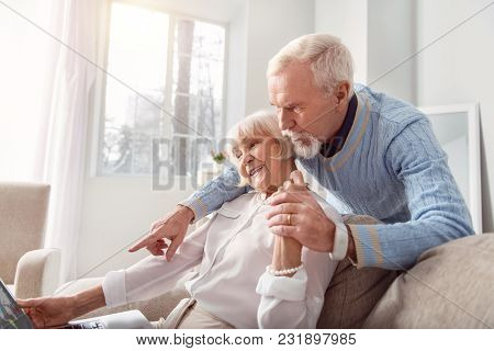 Planning Trip Together. Pleasant Senior Man Hugging His Beloved Wife From Behind And Pointing At The