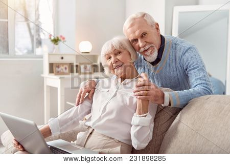 Pleasant Distraction. Joyful Elderly Man Hugging His Beloved Wife From Behind While She Sitting On T