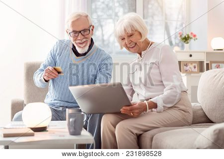 Fast Payment. Cheerful Senior Man Handing His Credit Card To His Wife While They Looking Through An