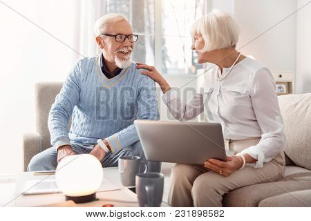 Good News. Joyful Senior Woman Holding A Laptop And Laughing Together With Her Husband While Discuss
