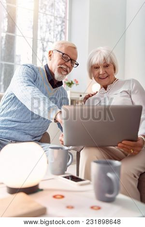 Having Fun. Upbeat Senior Couple Sitting In The Living Room And Watching A Funny Video On Their Lapt