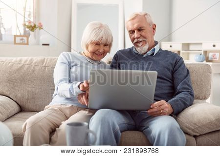 Quality Time. Upbeat Senior Husband And Wife Holding A Laptop In Their Lap And Surfing The Internet